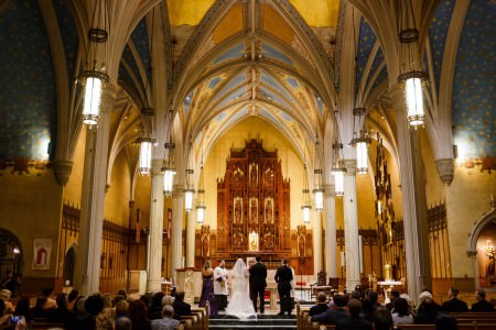 An image of a bride and groom standing at the altar with their best man and maid of honor in purple inside the Cathedral of St. John with cream colored pillars that form into beautiful arches on the ceiling which is painted blue with stars and the rest of the walls are a bright yellow with wooden accents.