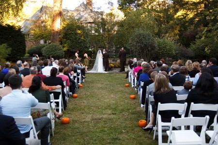 An autumn wedding ceremony in the backyard of the O'Neil House in Akron, Ohio with pumpkins lining the grass aisle leading to the altar with the tudor style home in the background with trees.