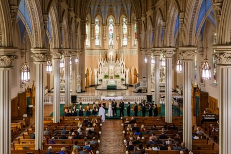 An image taken from the balcony of St. Patrick Parish overlooking a bride and groom standing arm and arm facing the congregation on a dark green carpeted platform with the wedding party standing on either side of the them in the ornate sanctuary full of tall arched light colored beams and blue painted ceiling inside the arched beams and tall thin stained glass windows above the altar and guests seated in the wooden pews facing the wedding party.