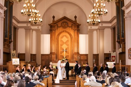 A picture taken from the back of the sanctuary of a bride and groom standing at the altar during the wedding ceremony at St. Paul's Episcopal church with tall pillars, an ornate wooden altar wall and high ceilings.