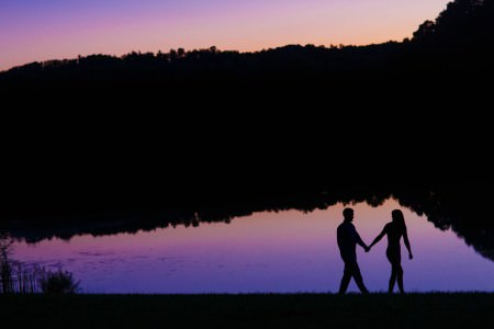 A photo of an engaged couple's black silhouette walking in front of Indigo Lake in Ohio at dusk where the lake is reflecting the purple and pink hued night sky.