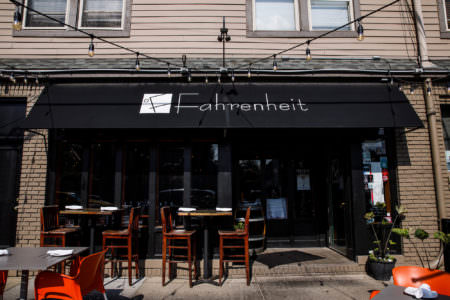 An image of the outside of the Fahrenheit restaurant with the brown painted brick walls and black awning hanging over their outdoor seating area with tall wooden chairs and white napkins set at the tables.
